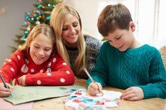 Μητέρα και παιδιά που γράφουν την επιστολή σε Santa από κοινού Στοκ Φωτογραφίες