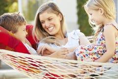 Μητέρα και παιδιά που χαλαρώνουν στην αιώρα κήπων από κοινού στοκ εικόνες