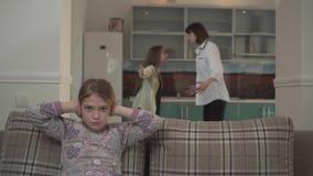 Μητέρα και παλαιότερη κόρη που υποστηρίζουν στην κουζίνα στο σπίτι Το κορίτσι Lillte καλύπτει τα αυτιά της με τα χέρια Προβλήματα απόθεμα βίντεο