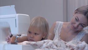 Μητέρα και περίεργος λίγη κόρη που χρησιμοποιεί τη ράβοντας μηχανή στο σπίτι στοκ φωτογραφία με δικαίωμα ελεύθερης χρήσης