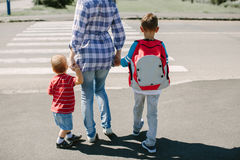 Μητέρα και τα παιδιά της για να διασχίσει περίπου το δρόμο Στοκ Εικόνες