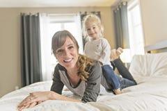 Μητέρα και το κορίτσι παιδιών κορών της που παίρνουν τον καλό χρόνο στο κρεβάτι στοκ φωτογραφία