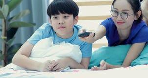 Μητέρα και το νέο αγόρι της που έχουν τη διασκέδαση και καναπές που προσέχει τη TV φιλμ μικρού μήκους