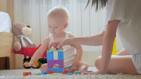Μητέρα και το παιχνίδι παιδιών της με τα παιχνίδια στο εσωτερικό Σερνμένος αστείο αγοράκι στο πάτωμα στο σπίτι Μητέρα και λίγος γ απόθεμα βίντεο