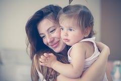 Μητέρα και το χαριτωμένο μωρό της στο σπίτι Μητέρα που κρατά λίγο μωρό μέσα Στοκ εικόνα με δικαίωμα ελεύθερης χρήσης