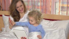 Μητέρα και χαριτωμένη κόρη που βρίσκονται στο κρεβάτι στο σπίτι και που κοιτάζουν στην ψηφιακή ταμπλέτα απόθεμα βίντεο