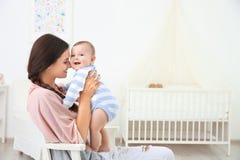 Μητέρα και χαριτωμένη συνεδρίαση μωρών στην καρέκλα μετά από να λούσει στοκ εικόνες