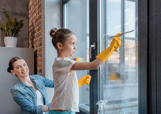 Μητέρα και χαριτωμένος λίγη κόρη στα προστατευτικά γάντια που καθαρίζουν το παράθυρο από κοινού Στοκ Εικόνες