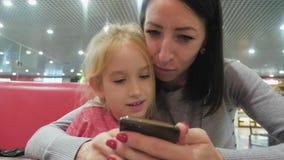 Μητέρα και όμορφη συνεδρίαση κορών στον καφέ και εξέταση το smartphone απόθεμα βίντεο