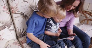 Μητέρα και δύο γιοι που διαβάζουν έναν υπολογιστή ταμπλετών Στοκ φωτογραφία με δικαίωμα ελεύθερης χρήσης