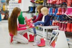 Μητέρα και δύο κορίτσια της που επιλέγουν τις νέες μπότες βροχής Στοκ φωτογραφία με δικαίωμα ελεύθερης χρήσης