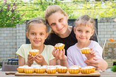 Μητέρα και δύο κόρες που κάθονται στον πίνακα με Πάσχα cupcakes στα χέρια του και εξετασμένος το πλαίσιο στοκ φωτογραφία με δικαίωμα ελεύθερης χρήσης