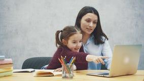 Μητέρα και teens κορίτσι με ένα lap-top μαζί σε ένα γκρίζο υπόβαθρο Κατά τη διάρκεια αυτού, εξετάζουν το lap-top ενώ φιλμ μικρού μήκους