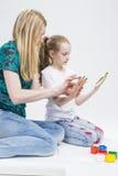 Μητέρα με λίγη κόρη που κάνει μια πίντα χεριών μαζί στο εσωτερικό Στοκ Φωτογραφία