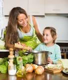 Μητέρα με λίγη κόρη που μαγειρεύει στο σπίτι Στοκ Εικόνες