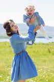 Μητέρα με λίγο μωρό στο camomile λιβάδι Στοκ Φωτογραφία