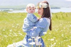 Μητέρα με λίγο μωρό στο camomile λιβάδι Στοκ Εικόνες