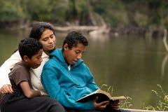 Μητέρα με δύο αγόρια της που μελετούν τη Βίβλο από το μέτωπο ποταμών στοκ εικόνα με δικαίωμα ελεύθερης χρήσης