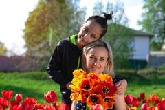 Μητέρα με δύο γιους στον κόκκινο τομέα τουλιπών Στοκ εικόνες με δικαίωμα ελεύθερης χρήσης
