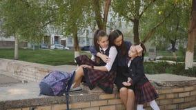 Μητέρα με δύο κόρες στη σχολική στολή με τα σακίδια πλάτης που κάθονται στην οδό κοντά στο σχολείο και τη συζήτηση απόθεμα βίντεο