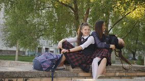Μητέρα με δύο κόρες στη σχολική στολή με τα σακίδια πλάτης που κάθονται στην οδό κοντά στο σχολείο που φιλά και που μιλά απόθεμα βίντεο