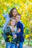 Μητέρα με δύο παιδιά κάτω από το χαμόγελο δέντρων φθινοπώρου στοκ εικόνες