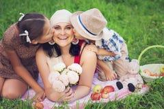 Μητέρα με δύο παιδιά που έχουν το πικ-νίκ υπαίθρια στοκ εικόνες