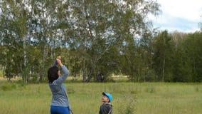 Μητέρα με λίγο πετώντας ικτίνο γιων υπαίθριο φιλμ μικρού μήκους