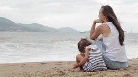 Μητέρα με μια συνεδρίαση κορών με δικούς του πίσω στη κάμερα στην αμμώδη παραλία απόθεμα βίντεο