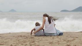 Μητέρα με μια συνεδρίαση κορών με δικούς του πίσω στη κάμερα στην αμμώδη παραλία φιλμ μικρού μήκους