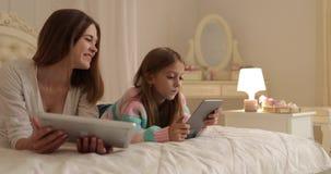 Μητέρα με να βρεθεί κορών στο κρεβάτι που χρησιμοποιεί την ευτυχή νέα οικογένεια υπολογιστών ταμπλετών απόθεμα βίντεο