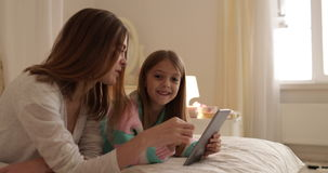 Μητέρα με να βρεθεί κορών στο κρεβάτι που χρησιμοποιεί την ευτυχή χαμογελώντας νέα οικογένεια υπολογιστών ταμπλετών φιλμ μικρού μήκους