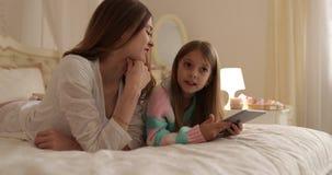 Μητέρα με να βρεθεί κορών στο κρεβάτι που χρησιμοποιεί την ευτυχή χαμογελώντας νέα οικογένεια υπολογιστών ταμπλετών απόθεμα βίντεο
