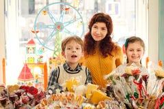 Μητέρα με τα ευτυχή παιδιά στο κατάστημα καραμελών Στοκ εικόνες με δικαίωμα ελεύθερης χρήσης