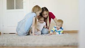 Μητέρα με τα παιδιά που διαβάζουν ένα βιβλίο σε έναν γκρίζο τάπητα στο σπίτι απόθεμα βίντεο
