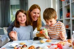 Μητέρα με τα παιδιά που διακοσμούν τα μπισκότα για αποκριές Στοκ Φωτογραφία