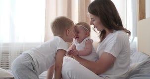 Μητέρα με τα παιδιά που παίζουν στο κρεβάτι απόθεμα βίντεο