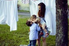 Μητέρα με τα παιδιά της έξω από την ένωση του πλυντηρίου, παιχνίδι αδελφών με λίγη αδελφή, ευτυχής αγαπώντας οικογένεια Στοκ Εικόνες