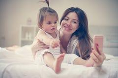 Μητέρα με την λίγο μωρό που έχει τη διασκέδαση στο κρεβάτι Στοκ εικόνα με δικαίωμα ελεύθερης χρήσης