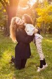 Μητέρα με την κόρη επτά χρονών στο πάρκο φθινοπώρου στο ηλιοβασίλεμα στοκ φωτογραφία