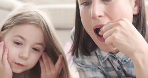 Μητέρα με την κόρη που έχει popcorn προσέχοντας τον κινηματογράφο φιλμ μικρού μήκους