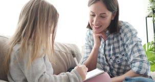 Μητέρα με την κόρη που επισύρει την προσοχή στο σημειωματάριο φιλμ μικρού μήκους