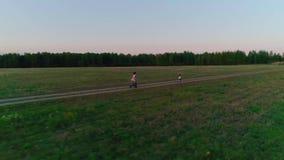Μητέρα με την κόρη που οργανώνεται στον αγροτικό δρόμο στο ηλιοβασίλεμα φιλμ μικρού μήκους