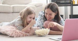 Μητέρα με την κόρη που τρώει popcorn και που προσέχει τον κινηματογράφο φιλμ μικρού μήκους