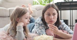 Μητέρα με την κόρη που τρώει popcorn και που προσέχει τον κινηματογράφο απόθεμα βίντεο