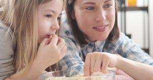 Μητέρα με την κόρη που τρώει popcorn στο σπίτι απόθεμα βίντεο