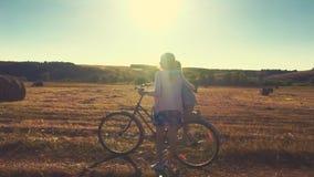 Μητέρα με την κόρη στα ποδήλατα σε ένα λιβάδι Οικογένεια στα ποδήλατα στη φύση Η έννοια της οικογένειας απόθεμα βίντεο