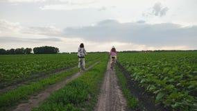 Μητέρα με την κόρη στους γύρους ποδηλάτων σε έναν βρώμικο δρόμο απόθεμα βίντεο