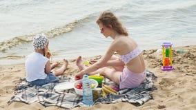 Μητέρα με την κόρη της σε ένα πικ-νίκ από τον ποταμό μια ηλιόλουστη ημέρα απόθεμα βίντεο