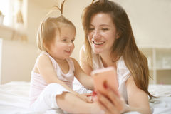Μητέρα με την λίγο μωρό που έχει τη διασκέδαση στο κρεβάτι Χρησιμοποίηση του έξυπνου π Στοκ φωτογραφία με δικαίωμα ελεύθερης χρήσης